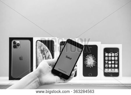 Paris, France - Apr 26, 2020: Woman Hand Holding Latest Iphone Se 2020 Phone With Multiple Packages
