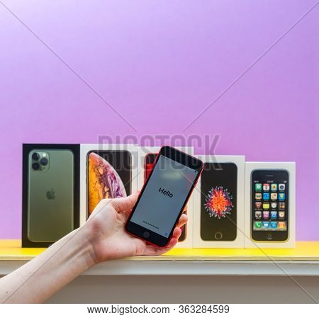 Paris, France - Apr 26, 2020: Woman Hand Holding Latest Iphone Se 2020 Red Phone With Multiple Packa