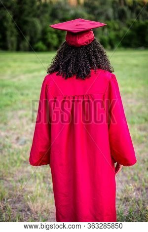 Rear view Portrait of a beautiful multi-ethnic woman wearing her graduation cap and gown. Vertical abstract photo of a diverse college or high school graduate