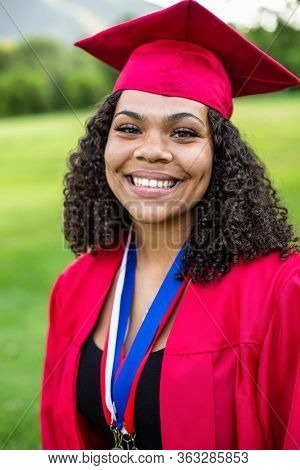 Portrait of a beautiful multi-ethnic woman wearing her graduation cap and gown. Selective focus on her beautiful face