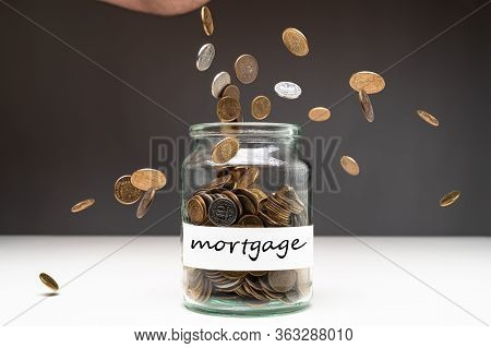 Coins In A Jar With Mortgage Text On A White Label. Money Falling From The Sky Above. Savings Abstra