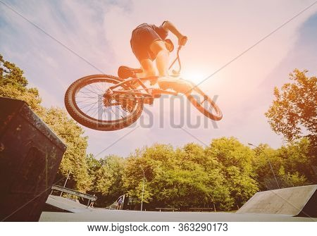 Boy Jumping With His Bmx In The Park.