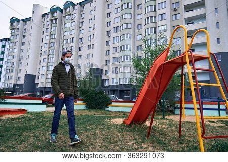 teen boy walks through the playground near high-rise buildings with apartments, a residential area, a medical mask on his face protects against viruses and dust
