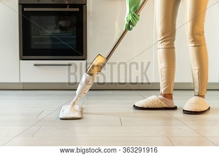 Woman In Rubber Gloves Using Microfiber Spray Mop Pad And Refillable Bottle With Cleaning Solution,