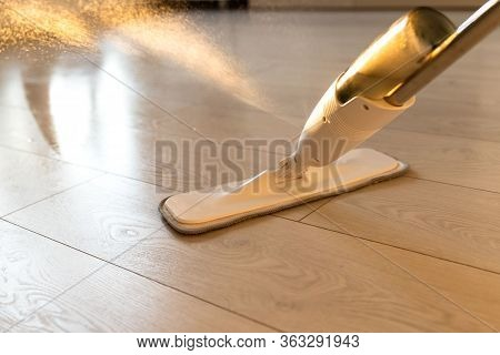 Person Using Spray Mop Pad And Refillable Bottle With Cleaning Solution, Mopping The Floor In Apartm