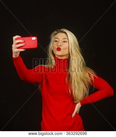 Blonde Woman With Kisses Lips In Red Blouse Holding Phone And Looking Nice On Dark Background.