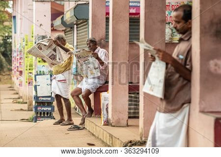 Alleppey, India - November 28, 2019: Unidentified indian men reading newspapers outside in Kerala , Southern India
