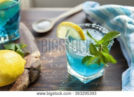 Alcoholic Cocktail On A Wooden Table Surrounded By Ingredients Such As Lemon, Salt, Sugar, Ice