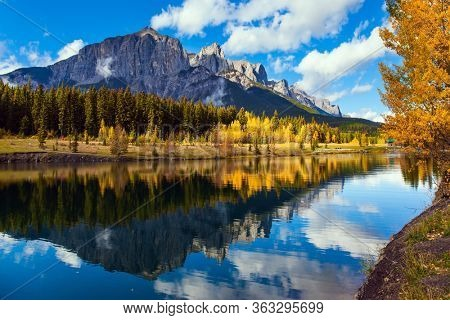 Outskirts of Canmore. Lush autumn in the Canadian Rockies. Cumulus clouds reflected in the smooth water of the lake. The concept of active, ecological and photo tourism