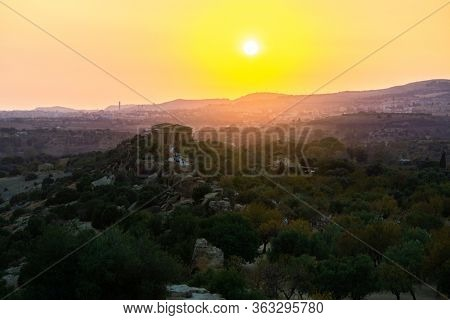 Sunset at Valley of the Temples (Valle dei Templi), ancient Greek Temple built in the 5th century BC, Agrigento, Sicily. Famous tourist attraction in Italy. Sicilian landscape, travel destination