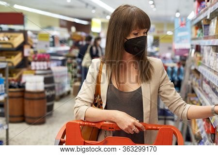 Young woman in face mask shopping in grocery store supermarket.
