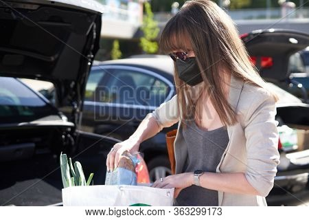 Young woman in face mask packing food to car trunk in parking place after grocery store shopping.