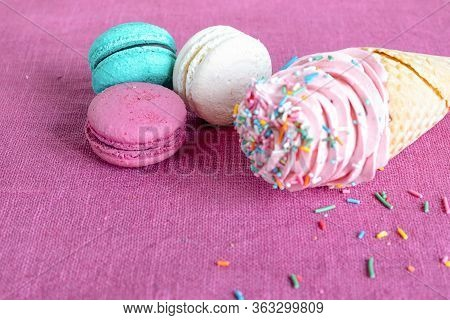 White, Blue And Purple Macaroons, Waffle Cone With Homemade Marshmallow And Spring Flower On A Linen