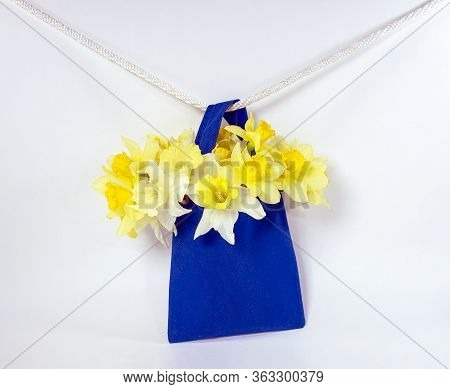 Spring Daffodils In Blue Bag Hanging On A White Clothesline