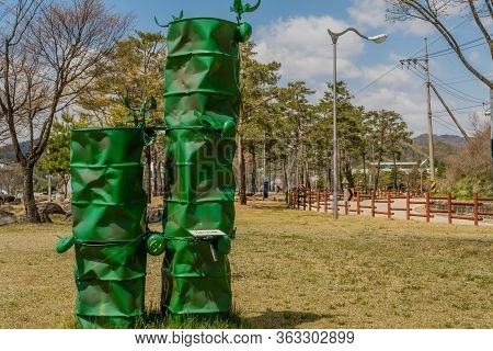 Jinan, South Korea; April 21, 2020: Sculpture Of Old Used Oil Drums Painted Green And Welded Togethe