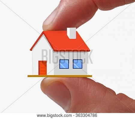 Fingers hold a tiny house.Real estate agent seller hold a small house on hand concept.