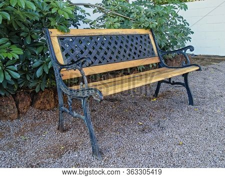 wood and iron bench in the front garden at the house, sitting on gravel