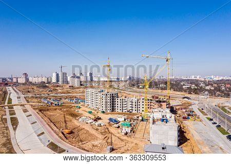 New Apartment Buildings Under Construction And Tower Crane Against Blue Sky. Aerial View From Flying