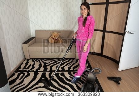 Young Brunette Woman Vacuum Cleaning At Home. Girl Using A Vacuum Cleaner While Cleaning Floor. Hous