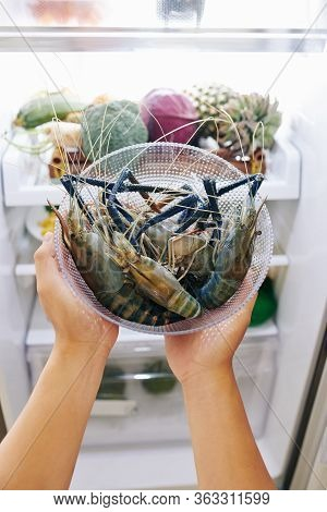 Hands Of Woman Putting Glass Bowl With Blue Spiny Lobsters In Refrigerator