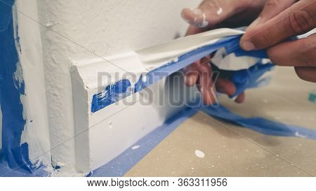 Painter Man Removing Masking Blue Tape From Molding, Baseboard.
