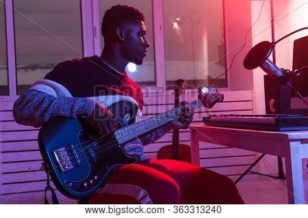Create Music And A Recording Studio Concept - African American Man Guitarist Recording Electric Bass