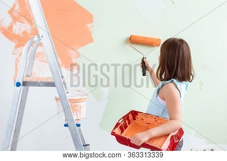Kid Standing With Paint Roller In Hand. She Is Painting The Wall, Rear View. Redecoration, Repair An