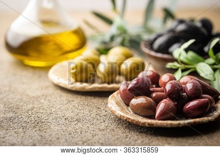 Variety Of Black And Green Olives And Olive Oil In Bowls On Stone Background Close Up