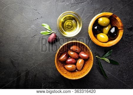 Black And Green Olives And Olive Oil In Wooden Bowls On Black Background. Top View With Copy Space F
