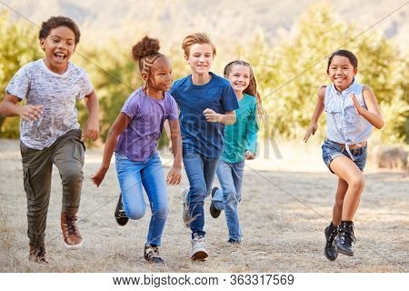 Portrait Of Multi-Cultural Children With Friends RunnIng Towards Camera In Countryside Together