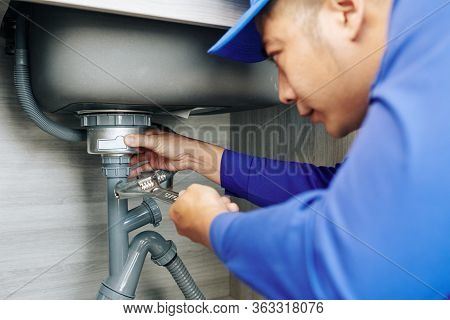 Serious Plumber Using Wrench When Repairing Leaky Drain In Kitchen