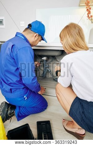 Young Woman Showing Repairman Leaky Drain Under Kitchen Sink