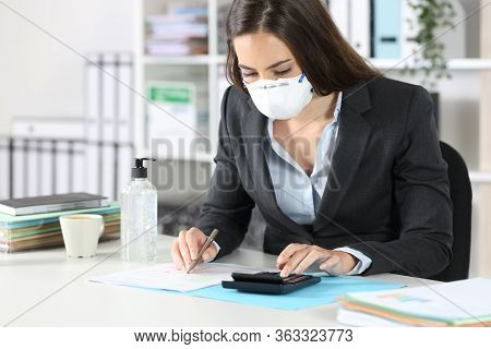 Bookkeeper With Protective Mask Calculating With Calculator Ticking Off Document At The Office