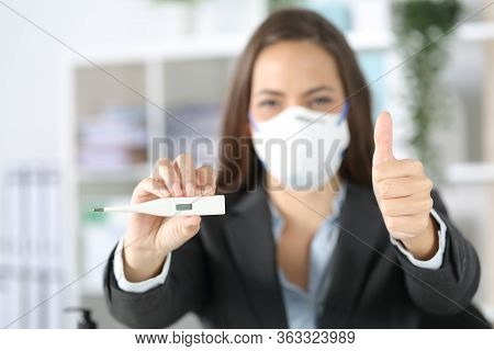 Front View Of Executive Woman Holding Thermometer With Thumbs Up With Protective Mask At The Office