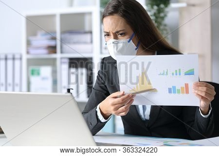 Sad Executive Woman With Protective Mask Shows Bad Results Report On Videocall On Laptop At The Offi