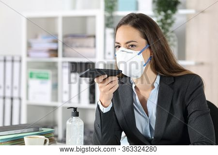 Executive Woman With Protective Mask Using Voice Recognition System On Smart Phone At The Office