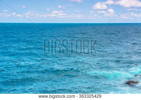 Rocky Sea Shore In The Afternoon. Blue Waves Crashing The Coast. Fluffy Clouds Above The Horizon.