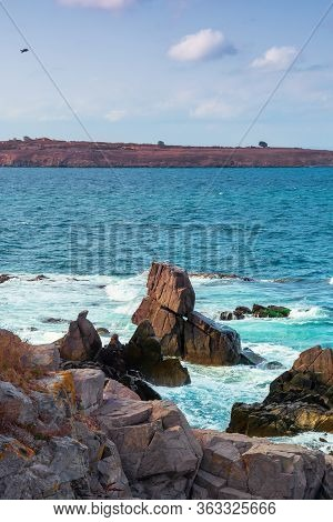 Seascape With Rocks And Cliffs. Beautiful Scenery In The Afternoon Light. Island In The Distance. Fl