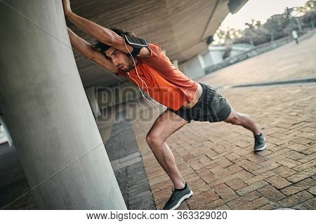 Portrait Of A Fitness Man With Armband And Earphone Doing Stretching Exercises Under The Bridge