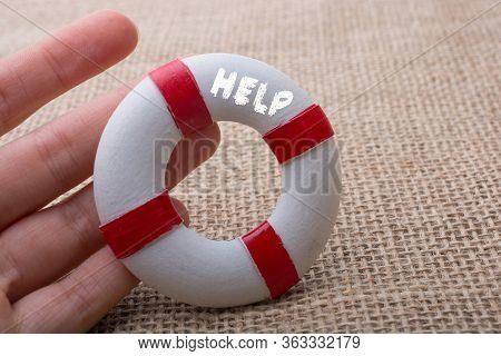 Hand Holding A Lifesaver  Or Life Preserver On A Fabric Background