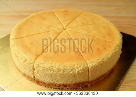 Delectable Fresh Baked Creamy Yellow Whole Plain Cheesecake Isolated On Wooden Table