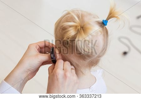 Baby Girl Wearing A Hearing Aid. Disabled Child, Disability And Deafness Concept.