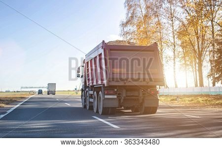 A 40 Ton Truck Carries Construction Sand On The Highway. Concept Of Overload On The Roads And Rental