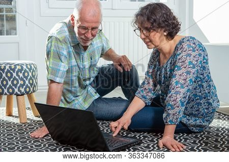Couple Senior Using A Computer Laptop At Home For Online Shopping
