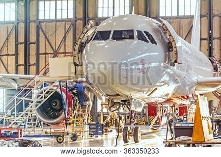 Aviation Hangar And Repairable Passenger Aircraft. Work Mechanics On Maintenance Parts
