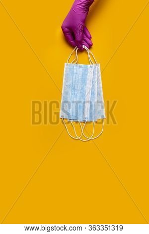 Doctor Holds Respiratory Surgical Face Mask In Hands Pink Medical Gloves On Yellow Background. Pande