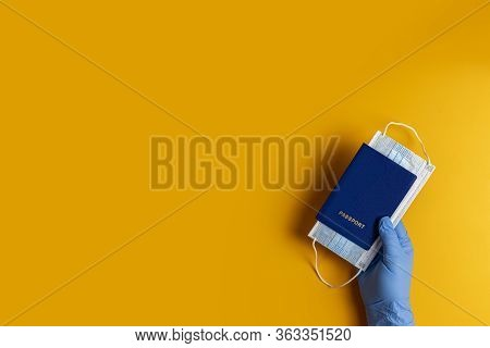 Doctor Holds Passports And Respiratory Surgical Face Mask In Hands Blue Medical Gloves On Yellow Bac