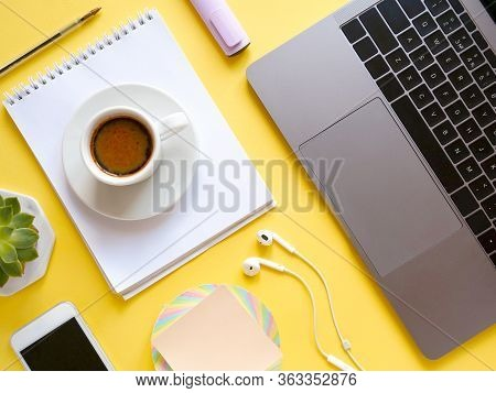 Flat Lay Composition With Laptop, Notebook, Pen, Coffee, Plant On Yellow Background. Concept Remote