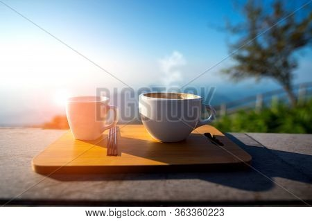 A Cup Of Coffee With Smoke On Wood Table, Blurred Estate Scenic Background, High Angle View. Morning