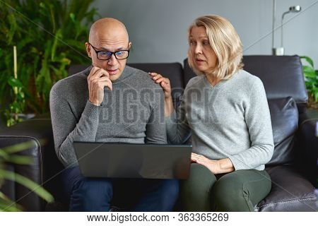 Middle-aged Mom Rest In Living Room With Adult Child Use Computer Family Weekend Together